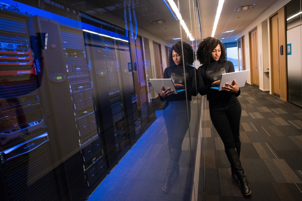 business woman on laptop in data center